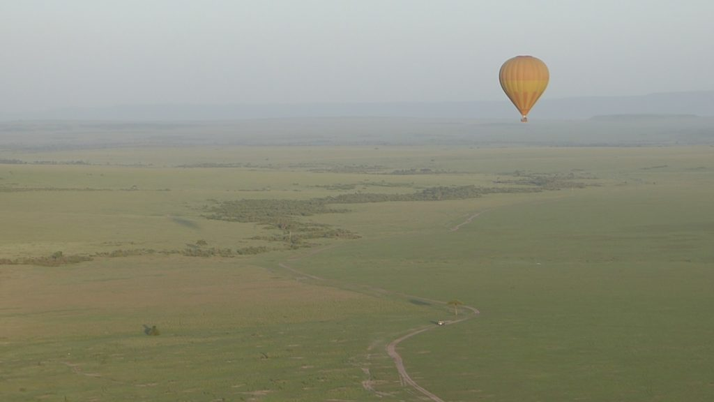 The Maasai Mara vom above. A small street is visible on the ground, in the distance you see an area full of trees. A yellow and orange balloon is flying in front.