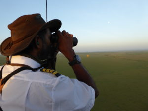 A pilot in a white shirt is looking though his binoculars. He is on the lookout to find animals down on the ground. You see another balloon in the far distance