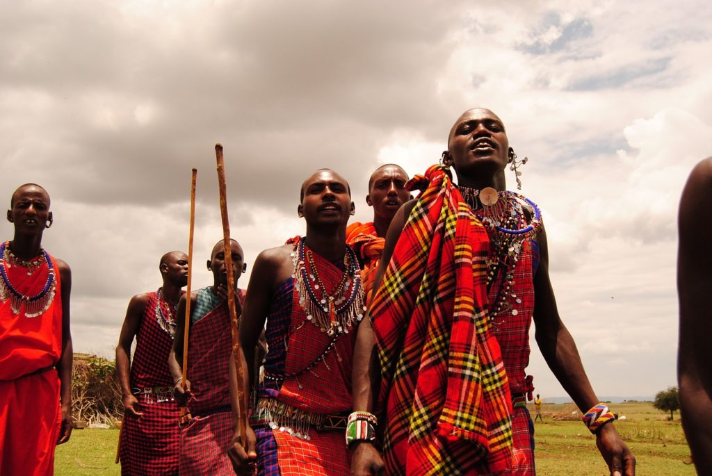 Six Maasai Men in red shukas with jewelry and sticks are dancing.