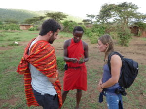 On a walking safari a Maasai guide is explaining different herbs to two visitors.