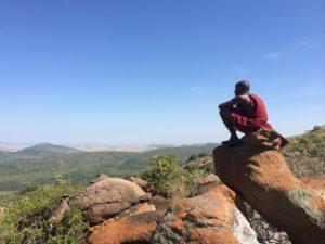 Maasai man sitting on a stone high above the Mara. He is enjoying the view.