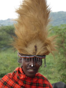 One young Maasai is smiling to the camera with a lion hat on his head. The hat is made out of the mane, is very high and is decorated with beads.