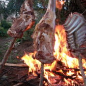 Three wooden sticks with goat meat are roasting above the flames of a campfire