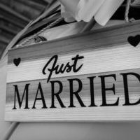 "Experience Maasai Culture and Say ""Yes"" like a Maasai. A wooden ""Just Married"" sign on a car. The picture is in black and white."