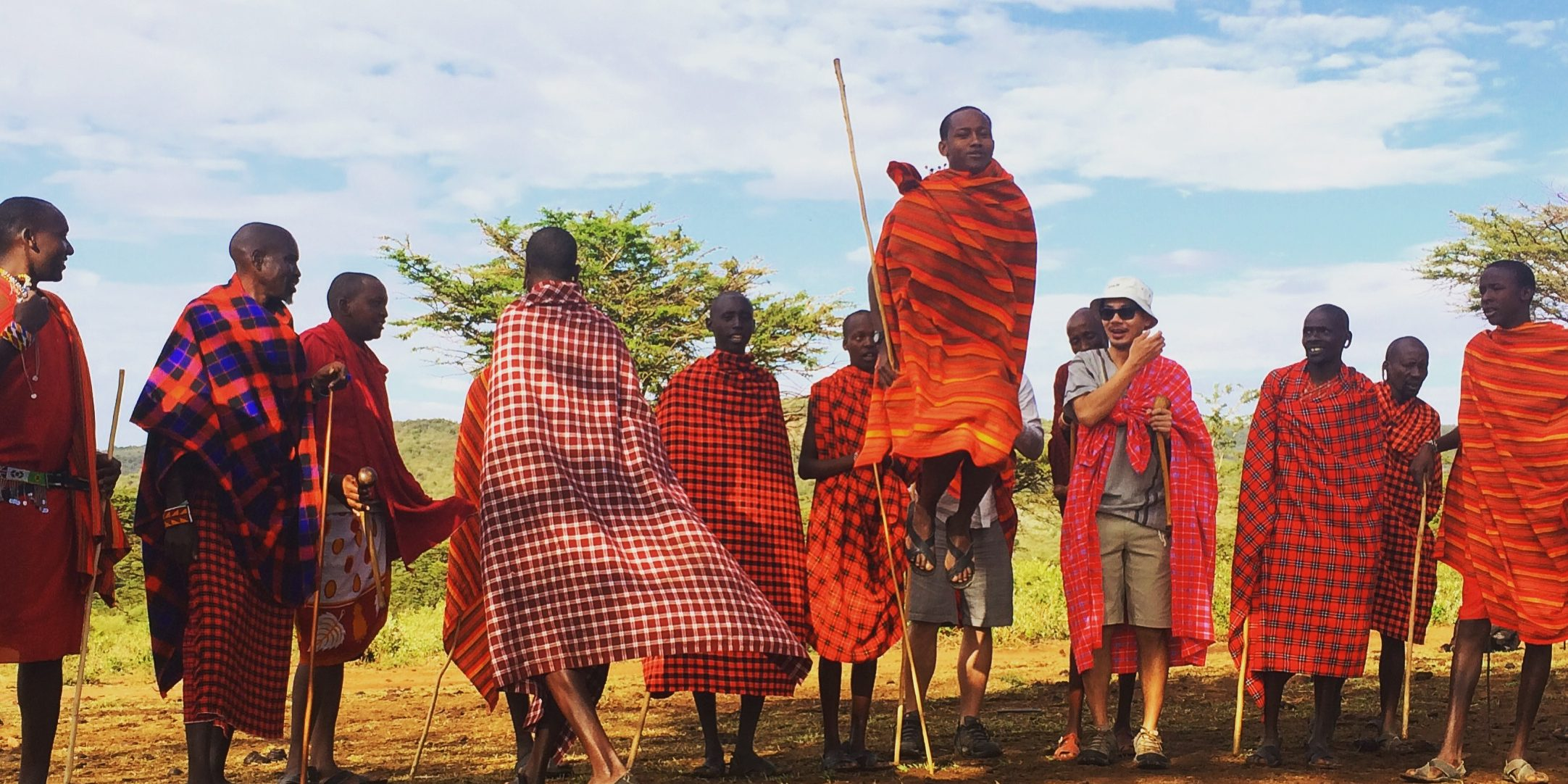 Maasai men in red shukas are performing their jumping dance. One man is jumping very high infront of the others watching. Two visitors are amazed by the performance.