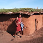 Experience Maasai culture in Kenya. Maasai man standing in front of a typical Maasai house out of mud, cow dung and clay. Gras is grwoing on the roof.