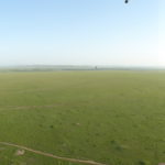180 Degrees view of the Maasai Mara out of a Hot Air Balloon. Everything is green and on the right you see a small river.
